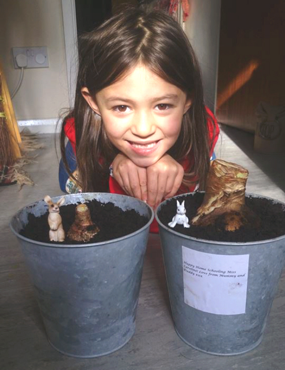 Image of girl's smiling face behind-2-metal plant pots-with large bulbs sprouting from the soil