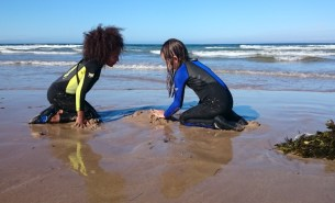 Image of girls-in-wetsuits-on-beach-with-mound-of-sand-and-pile-of-seaweed-in-front-of-surf