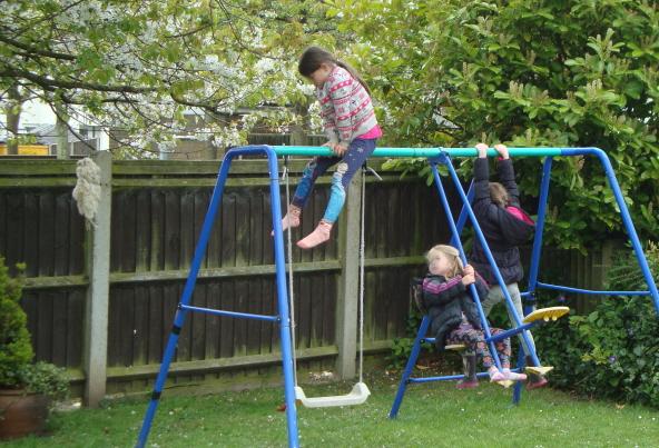 girls-on-swings-in-garden