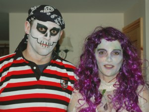 Image of man-in-pirate-skeleton-costume-and-woman-in-purple-wig-halloween-costume