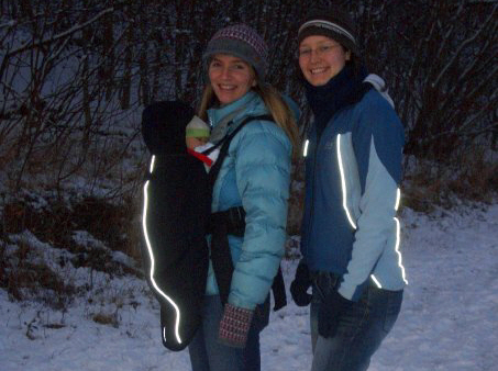 two-women-outdoors-in-snow-wearing-outdoor-gear-and-baby-in-an-inward-facing-carrier