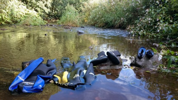 Image of wetsuits-rinsing-in-a-stream