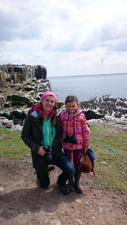 Image of woman-and-child-standing-on-cliff-with-seabirds-behind