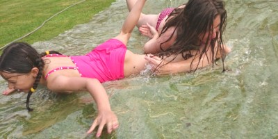 Image of woman-and-girl-on-water-slide-in-garden