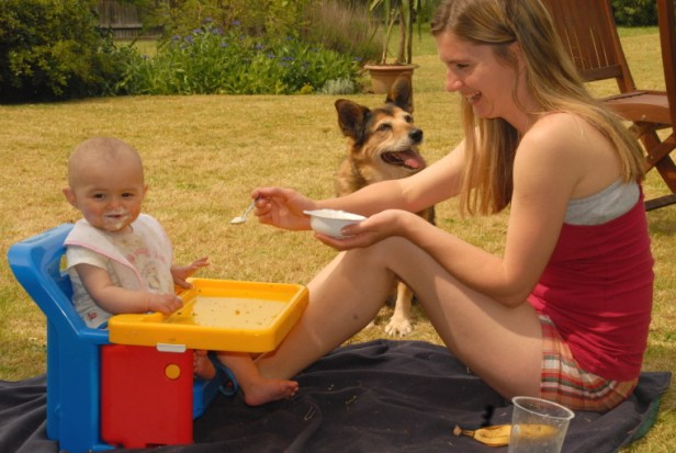 woman-feeding-baby-outdoors-with-dog-in-background