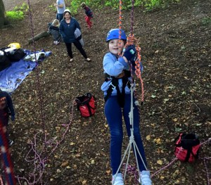 Image of girl-in-climbing-harness-in-tree