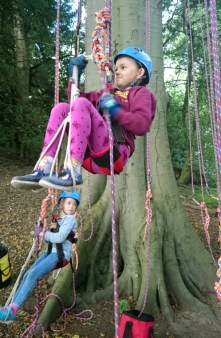Image of girl-in-squat-position-in-climbing-harness-on-ropes