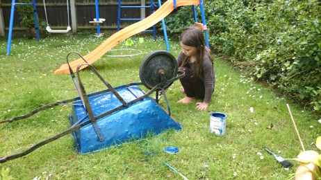 Image of girl-painting-wheelbarrow-in-garden