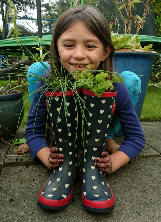Image of girl-squatting-behind-pair-of-wellies-planted-with-herbs