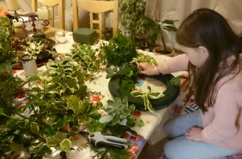 girl-at-table-placing-evergreens-into-oasis-ring