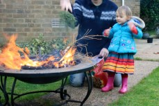 Image of toddler-throwing-Christmas-tree-twigs-onto-firepit-in-garden