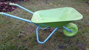 Image of child-size green and blue metal wheelbarrow on grass