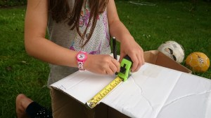 Image of girl with tape measure marking measurements on cardboard box