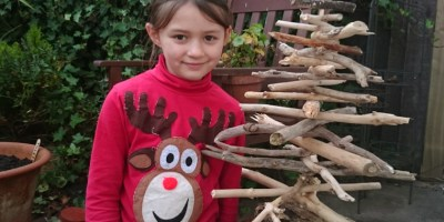 Image of girl-in-red-reindeer-jumper-next-to-driftwood-christmas-tree-in-a-garden
