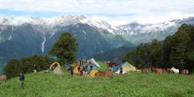Image of hillside-campsite-with-donkeys-and-tents-in-front-of-snow-capped-mountain-backdrop