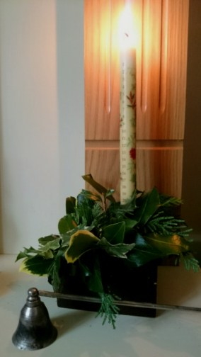 Image of numbered-advent-candle-with-evergreen-decoration