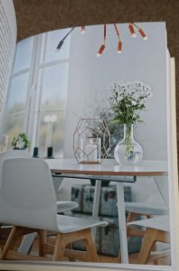 Image of open-book-showing-page-with-photo-of-flowers-on-table-in-white-room