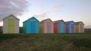 Image of pastel-coloured-row-of-beach-huts-with-grass-in-front-at-sunset