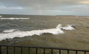 Image of rough-grey-sea-with-small-island-and-faint-rainbow-at-horixon