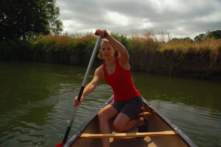 Image of woman-in-canoe-on-river-with-bank-in-background