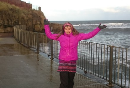 Image of woman-with-arms-in-air-in-wet-purple-coat-near-railings-at-the-sea