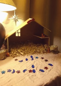 Image of wooden-advent-crib-on-table-with-straw-but-otherwise-empty