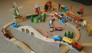 Image of wooden-train-set-laid-out-with-bridges-buildings-trains-vehicles-and-people