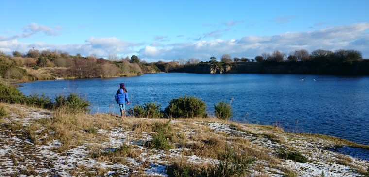 Image of girl-in-blue-coat-in-front-of-quarry-lake-on-sunny-day-with-snow-in-foreground