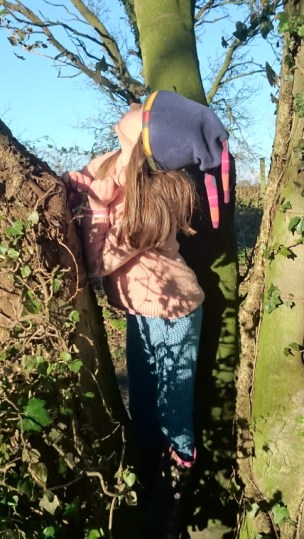 Image of girl-in-pink-jumper-blue-leggings-and-woolly-hat-amongst-ivy-covered-tree-trunks