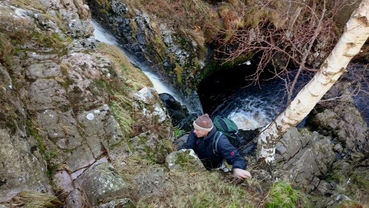 Image of man-scrambling-up-rocks-next-to-waterfall
