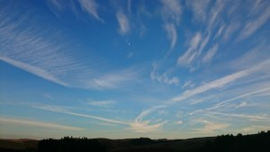 Image of moon-and-con-trails-in-evening-sky-over-silhouetted-landscape