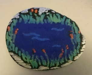 Image of painted-stone-with-picture-of-pond-and-reeds-on