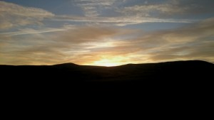 Image of sunset-over-silhouetted-hills