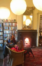 Image of woman-child-and-dog-sitting-in-front-of-open-fire-with-bookshelves-behind