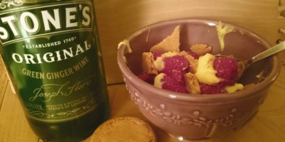 Image of bottle-of-ginger-wine-next-to-red-bowl-of-custard-raspberries-and-ginger-biscuits