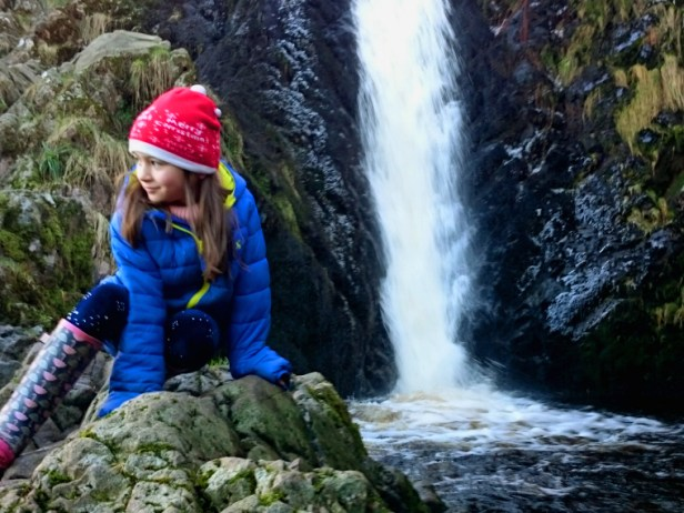 close-up-of-girl-in-blue-anorak-and-red-hat-hitting-on-rocks-with-waterfall-behind