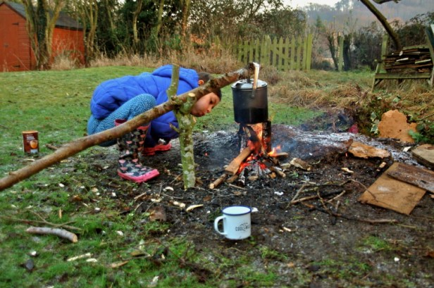 Image of girl-blowing-flames-on-fire-in-back-garden-with-cookpot-on-sticks