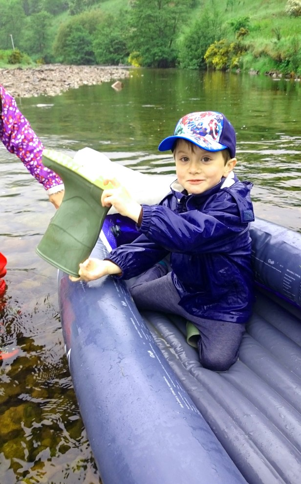 Image of boy in blue inflatable canoe at riverside bailing out with a welly boot