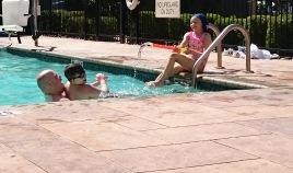 Image of girl at pool edge firing water pistol at man and boy in pool