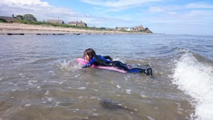 Image of girl on bodyboard with beach and houses in background