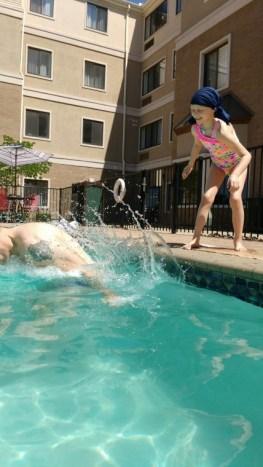 Image of girl pushing man into outdoor pool