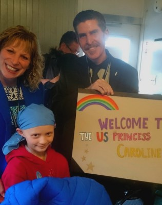 Image of man, woman and girl with welcome sign