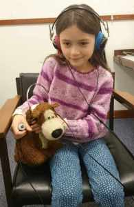 Image of girl in chair wearing headphones holding teddy bear also wearing headphones