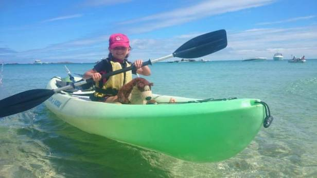 Image of girl in wetsuit and buoyancy aid with brown and cream bear in green kayak paddling in clear water