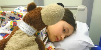 Image of girl lying in hospital bed cuddling brown and cream teddy with name band round neck