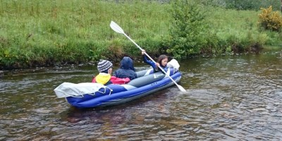 Girl paddling two boys in inflatable canoe