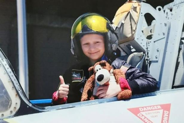 Girl with thumbs up wearing pilot helmet and bomber jacket sitting in cockpit holding brown and cream bear