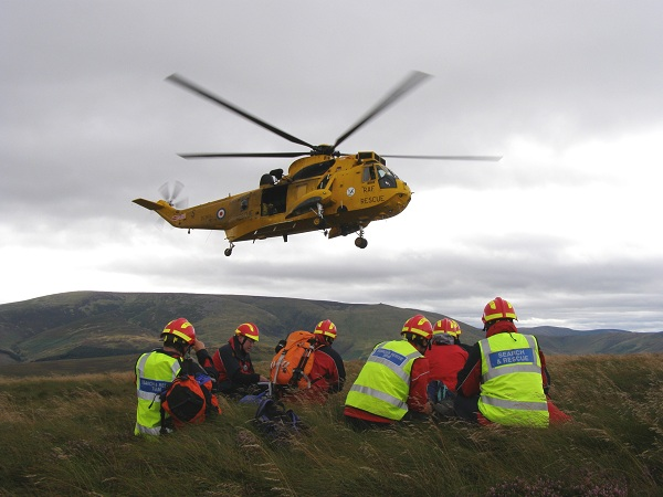 Image of Yellow RAF rescue helicopter with Northumberland National Park Mountain Rescue Team members on ground