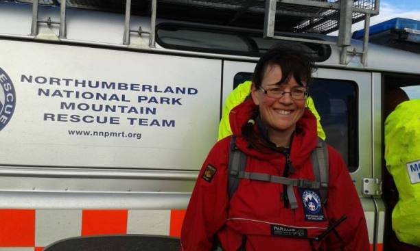 Image of woman in red outdoor gear in front of Northumberland National Park Mountain Rescue Team vehicle