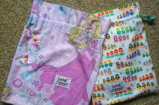Image of two cloth drawstring bags, one with princess pattern, one with multicoloured Russian dolls pattern with Beads of Courage labels on
